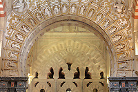 Looking through a sculpted arch designed with 22 figures in niches by Hernan Ruiz the Younger, 1514-69, under bishop Don Leopoldo de Austria, 1541-57, into the Villaviciosa Chapel, built under Alfonso X in the 13th century, in the Cathedral-Great Mosque of Cordoba, in Cordoba, Andalusia, Southern Spain. The chapel contains fluted intertwined arches with intricate carved decorative detail. The first church built here by the Visigoths in the 7th century was split in half by the Moors, becoming half church, half mosque. In 784, the Great Mosque of Cordoba was begun in its place and developed over 200 years, but in 1236 it was converted into a catholic church, with a Renaissance cathedral nave built in the 16th century. The historic centre of Cordoba is listed as a UNESCO World Heritage Site. Picture by Manuel Cohen