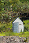 """White wooden outhouse in the Rocky Mountains with """"no trespassing"""" sign, Colorado Rockys"""
