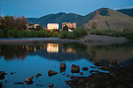 the setting sun reflects off buildings in downtown missoula, montana across the clark fork river