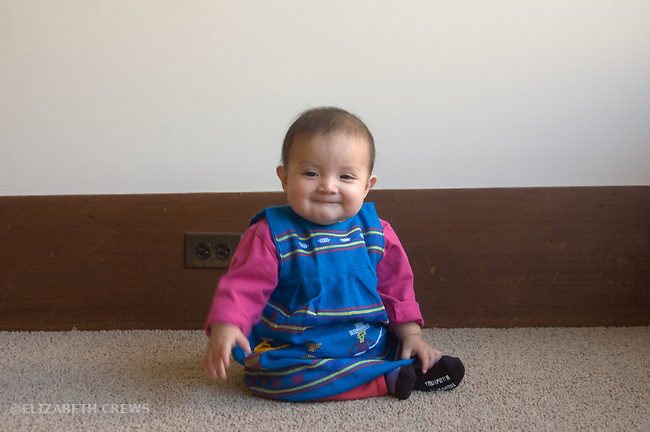 Berkeley CA Eight-month-old Guatemalan girl sitting up, showing lively facial expression MR
