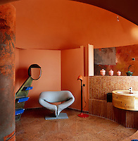 A Pierre Paulin Ribbon chair stands in the corner of this orange bathroom