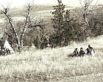 A young Native American Indian woman with three young children sitting on a blanket in the fall season of South Dakota