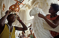 Rio de Janeiro carnival, Samba School barracao - the place where the school is created and produced - black boy tries on his costume of king.