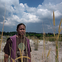 Indonesia - Bangka Island - Astrid Ali, 33 taking a look at the mine where she will start working from tomorrow since the illegal mine where she was working has just been seized by the police. She is one of the few women in the mining sector doing sucking, a hard job generally reserved for men. She has worked in tin mining for 5 years, moving to several illegal mines. A single parent, she has three kids who are being looked after by her parents. She sleeps and lives in the mining location, and goes to visit them once every week.