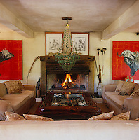 A pair of red paintings of buffalo by Tonio Trzebinski dominate the walls of the living room either side of the open fireplace