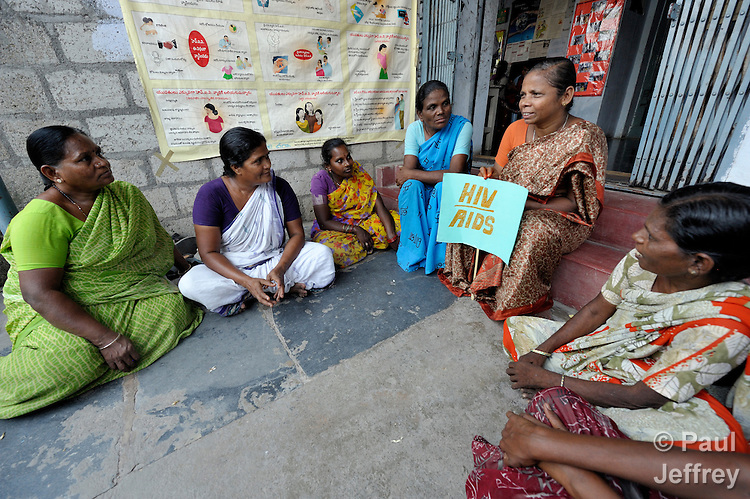 V Siva Lakshmi (holding the sign), a 52-year old woman living with HIV, discusses how to combat stigma and discrimination with other women in the Lutheran Counseling and Health Care Center in Chilakaluripet, a town in Andhra Pradesh, India. Her daughter is beside her. (Note Special Instructions below.)
