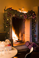 A roaring fire burns in the imposing fireplace in the kitchen which is decorated with spruce and baubles