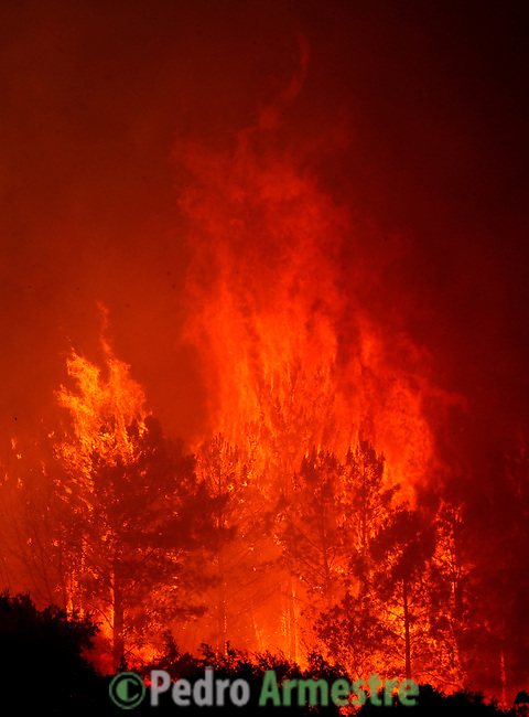 "SPAIN, Mombeltran : People view flames and heavy smoke engulfing the forest in ombeltran near Avila, . With temperatures forecast to hit 40 degrees Celsius (104 degrees Fahrenheit) in many parts of Spain on Tuesday, the interior ministry maintained three-quarters of Spain on ""maximum"" alert for wildfires. on July 28, 2009. (C) Pedro ARMESTRE"