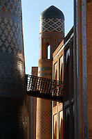 Detail of bridge between the Matniyaz Divan-begi Madrasah (right), 1871, and Kalta Minor (left), 1855, Khiva, Uzbekistan, pictured on July 6, 2010 at sunrise. Commissioned by Muhammad Niyaz the rectangular, Madrasah has a traditional main facade, its high portal, decorated with majolica, having a central pentahedral niche and corner guldastas which are geometrically patterned in blue, white and green, with green brick domes. The Kalta Minor or Short Minaret was commissioned by Mohammed Amin Khan in 1852 to stand 70 m. high, but was abandoned when he died in 1855, and remains only 26 m. high. Khiva, ancient and remote, is the most intact Silk Road city. Ichan Kala, its old town, was the first site in Uzbekistan to become a World Heritage Site(1991). Picture by Manuel Cohen.