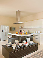 The open-plan kitchen is contemporary and high-spec with an central glossy, black island and storage unit