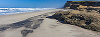 The bluffs at Pomponio Beach face clear blue skies and gently rolling waves cropped to a panoramic view.