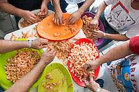 Kitchen staff peeling shrimp. Don Manuel Sanchez Villalpando known as El Cuchupetas owner and founder of his Cuchupetas restaurant in Villa Union, Sinaloa.