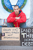 """A man sits behind protest signs in Zuccotti Park encouraging """"Occupy Wall Street, not Afghanistan"""" during the Occupy Wall Street demonstration in New York City, New York."""