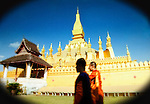 Two Buddhist priests walk through the grounds of the Golden Pagoda in Vientiane, Lao Republic.