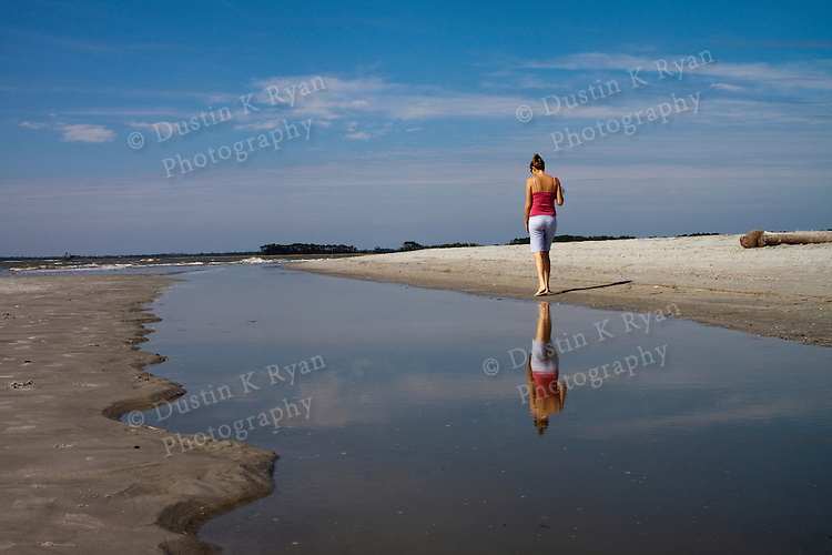 Woman walking on beach near reflecting tidal pool reflection Folly Beach South carolina
