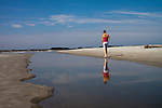Woman walking on beach near reflecting tidal pool reflection Folly Beach South carolina
