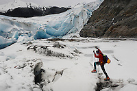 Hiker climbs on top of melting Mendenhall Glacier in Southeast Alaska.