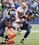 Seattle Seahawks running back Marshawn Lynch is tackled by San Francisco 49ers strong safety Donte Whitner and linebacker Larry Grant after gaining  eight-yards at  CenturyLink Field in Seattle, Washington on December 24, 2011. Trying to block Whitner is Seahawks fullback  Michael Robinson. The 49ers came from behind to beat the Seahawks 19-17. ©2011 Jim Bryant Photo. All Rights Reserved.