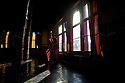 A monk prepares to perform morning duties in the Maitreya Buddha room at Thiksey Monastery, Ladakh, India.