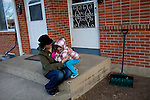 """Kendrick Brinson.LUCEO..Adrianne Ireland sits on the front porch with her daughter Sloan, 3, outside of her family's apartment in oil boom-town Williston, North Dakota in January 2012..Adrianne temped at Precision Drilling last year, but now bartends at a popular bar called Whispers..The population of Williston has almost doubled since Adrianne was in high school, she said, and milk prices have gone up with population..Adrianne's mother, Peggy Adrin said the town has """"really changed a lot"""" since she first moved there 30 years ago. """"When we first moved here, there was nothing,"""" she said. Williston, North Dakota is currently experiencing an influx of people relocating there for the town's third oil boom...Model Released: Yes.Assigning Editor: Michael Wichita."""