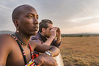 Masai tribesman and a tourist look for wildlife in the early morning in the Masai Mara, Kenya, Africa