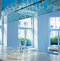 Pale-blue glass shelving above the kitchen island reflects the matching blue of the painted timber floor of the dining area