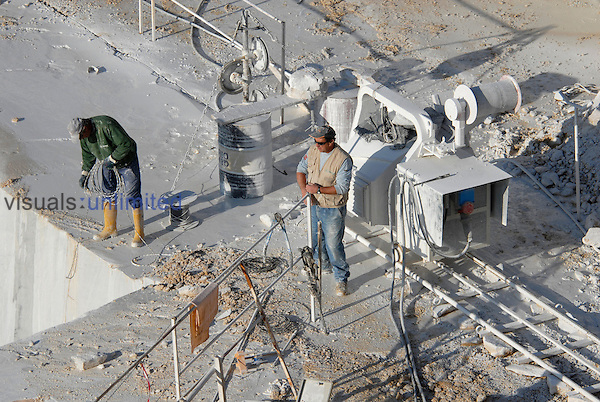 Workers on duty on a marble quarry near a diamond wire saw