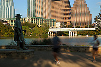Runners pass the SRV Statue as kayakers paddle on Town Lake Austin