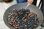 Asia, China, Yichang. Vendor roasts hazelnuts in Yichang.