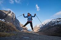 Female hiker jumps in air with Horseid beach in background, Moskenesøy, Lofoten Islands, Norway