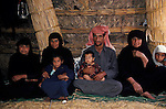 Marsh Arabs. Southern Iraq. Circa 1985. Marsh Arab man and two wives and children in reed constructed home.
