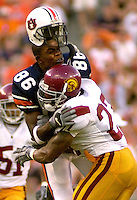 Photo by Gary Cosby Jr.  Auburn University wide receiver Courtney Taylor has his helmet knocked off in a collision with University of Southern California defensive back Ronald Nunn.  The pass fell incomplete.