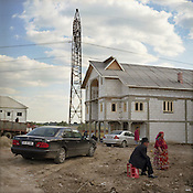 A Roma couple supervise the construction of their new home, beside the road that runs through Sintesti Roma camp. Over 100 new houses, of fanciful architectural design , have been bult in the last 7 years with the profits from scrap metal dealing.