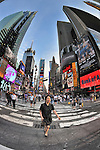 Woman and others crossing street in Times Square, New York City, NY, USA, a fisheye lens view, June 27, 2011.