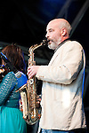 Legendary Irish traditional group Kila perform at the St Patrick's Day Festival, Trafalgar Square, London, UK (16 March 2014). Pictured here, Colm Ó Snodaigh on saxophone.