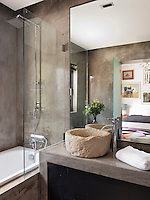 The sandy colour and texture of the rough hewn stone basin contrasts with the smooth grey polished concrete of this contemporary ensuite bathroom