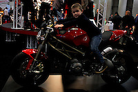 New york, United States. 18th January 2013 -- A boy test a Ducati motorcycle during The International Motorcycle Show in New York. -- BMW, Ducati, Harley-Davidson, Honda, Kawasaki, Suzuki, Star, Triumph, Victory, Yamaha and more have all utilized the International Motorcycle Shows to unveil new motorcycles and concept vehicles to the world. Photo by Eduardo Munoz Alvarez / VIEWpress.