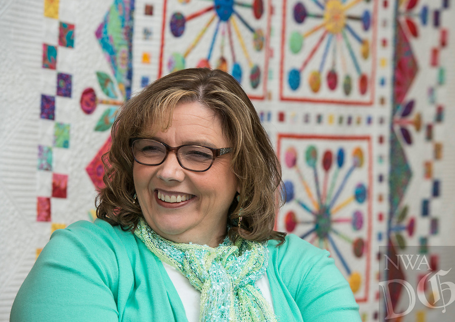 NWA Democrat-Gazette/ANTHONY REYES @NWATONYR<br /> Carla Gray backdropped by her winning quilt &quot;Atomic Bloom&quot; Monday, April 3, 2017 at the Shiloh Museum in Springdale. Gray's quilt won Best of Show and First Place Mixed Techniques, Bed Size Category at the Tomorrow's Heirlooms XVI quilt show.