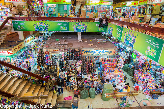 12 APRIL 2012 - HO CHI MINH CITY, VIETNAM: Overview of an interior aisle in Binh Tay Market. The market is warren of narrow halls and alleys and steep staircases and still relies on manual labor to move goods. Binh Tay market is the largest market in Ho Chi Minh City and is the central market of Cholon. Cholon is the Chinese-influenced section of Ho Chi Minh City (former Saigon). It is the largest &quot;Chinatown&quot; in Vietnam. Cholon consists of the western half of District 5 as well as several adjoining neighborhoods in District 6. The Vietnamese name Cholon literally means &quot;big&quot; (lon) &quot;market&quot; (cho). Incorporated in 1879 as a city 11&nbsp;km from central Saigon. By the 1930s, it had expanded to the city limit of Saigon. On April 27, 1931, French colonial authorities merged the two cities to form Saigon-Cholon. In 1956, &quot;Cholon&quot; was dropped from the name and the city became known as Saigon. During the Vietnam War (called the American War by the Vietnamese), soldiers and deserters from the United States Army maintained a thriving black market in Cholon, trading in various American and especially U.S Army-issue items.     PHOTO BY JACK KURTZ
