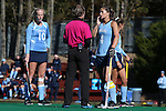15 November 2014: Referee Ridge Bair (center) discusses a call with North Carolina's Samantha Travers (ZIM) (4) and Nina Notman (GER) (10). The University of North Carolina Tar Heels hosted the Liberty University Flames at Francis E. Henry Stadium in Chapel Hill, North Carolina in a 2014 NCAA Division I Field Hockey Tournament First Round game. UNC won the game 2-1.