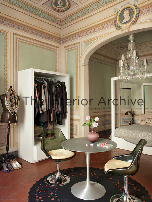 A modern white painted four poster bed and retro Eero Saarinen chairs and table contrast with the traditional painted plaster decoration and ornate chandelier in a green and pink bedroom.