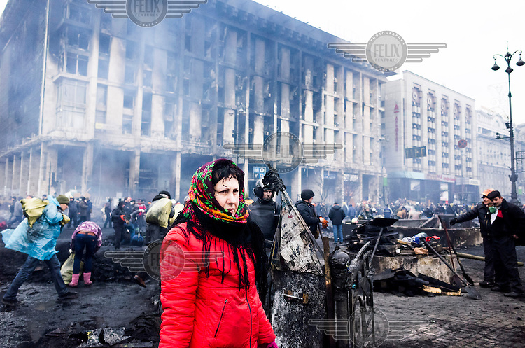 A woman wearing a head scarf walks through the charred detritus on Kiev's Maidan Nezalezhnosti (Independence Square), renamed EuroMaidan by protesters since November 2013. Protests against the government of President Viktor Yanukovych were sparked on 21 November 2014 by the Ukrainian government's decision to suspend preparations for the signing of an association agreement with the European Union that would have increased trade with the EU. Some believe that the U-turn came about as a result of pressure from President Putin of Russia who wants Ukraine to join a customs union with itself, Kazakhstan and Belarus. Russia offered 15 billion dollars of soft loans and reduced price gas to Ukraine at the same time as discussions with the EU were taking place. After weeks of protests and a number of deaths, Prime Minister Mykola Azarov and the entire cabinet resigned. Protesters are holding out, however, for President Yanukovych to resign and continue to occupy public buildings and squares to put pressure on the president. On 18 February, after Yanukovych's party scuppered a move to change the constitution to reduce the powers of the president, renewed fighting between protesters and police broke out and had cost the lives of around 80 people by Friday 21st February.
