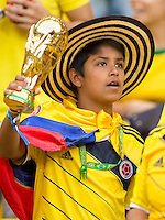 A young Columbia fan holding a world cup trophy