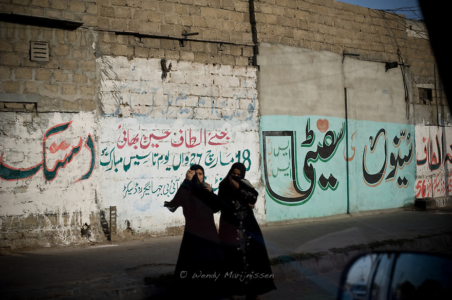 Two women in black hijab stand by the side of the road. Vulnerable in an overall conservative and male dominated society, women appear more covered and veiled outside when they venture out on the streets. Karachi, Pakistan, 2011