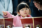 Four-year-old Mao Konishi and her mother Kae offer incense and say a prayer during a remembrance service to mark the one year anniversary of last year's magnitude 9 earthquake and tsunamis in Ofunato City, Iwate Prefecture, Japan on 11 Mar. 2012. .Photographer: Robert Gilhooly