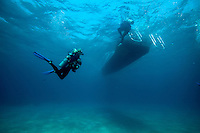 Scuba divers end their dive and board a boat; Roatan, Honduras.
