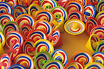 One yellow spinning top among other motionless multicolored spinning tops.