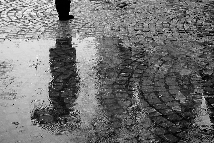 The reflection of a figure with an umbrella standing alone on a wet cobbled street in black and white