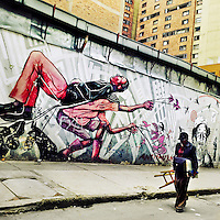 A Colombian street painter passes in front of a graffiti artwork, depicting the equality & liberation themes, created by an artist named Guache in the center of Bogotá, Colombia, 13 March, 2016. A social environment full of violence and inequality (making the street art an authentic form of expression), with a surprisingly liberal approach to the street art from Bogotá authorities, have given a rise to one of the most exciting and unique urban art scenes in the world. While it's technically not illegal to scrawl on Bogotá's walls, artists may take their time and paint in broad daylight, covering the walls of Bogotá not only in territory tags and primitive scrawls but in large, elaborate artworks with strong artistic style and concept. Bogotá has become an open-air gallery of contemporary street art.
