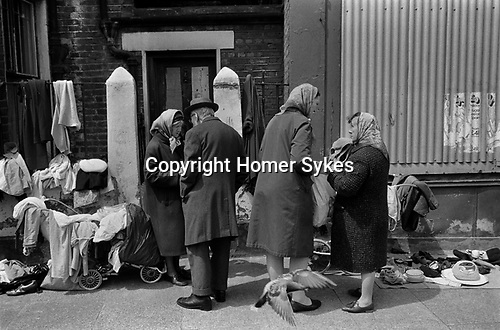 Woman selling old clothes from a pram  Whitechapel  near Brick Lane. East London  1972. pigeon flying up.